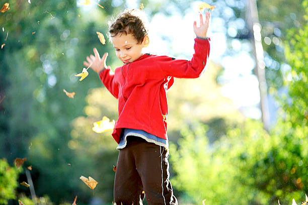 child tossing autumn leaves into the air - autism stock photos and pictures