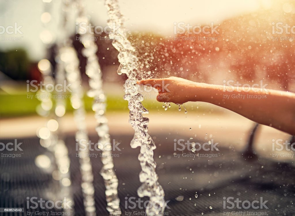 Child touching fountain on a hot summer day. stock photo