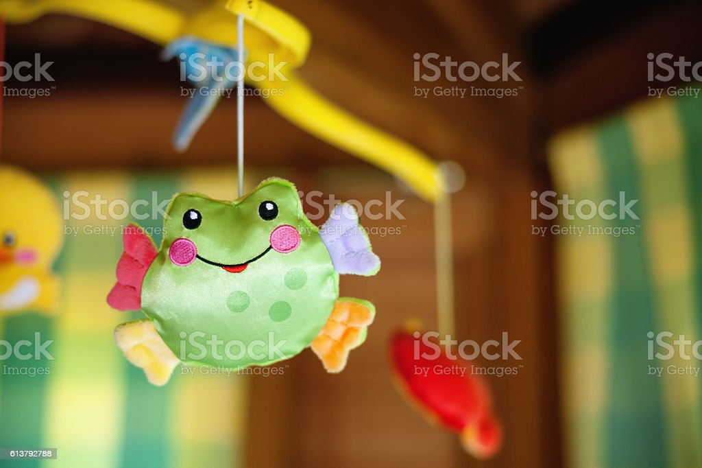 Child toy with frog hanging on baby cradle stock photo