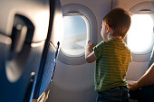 Little boy looking through airplane window
