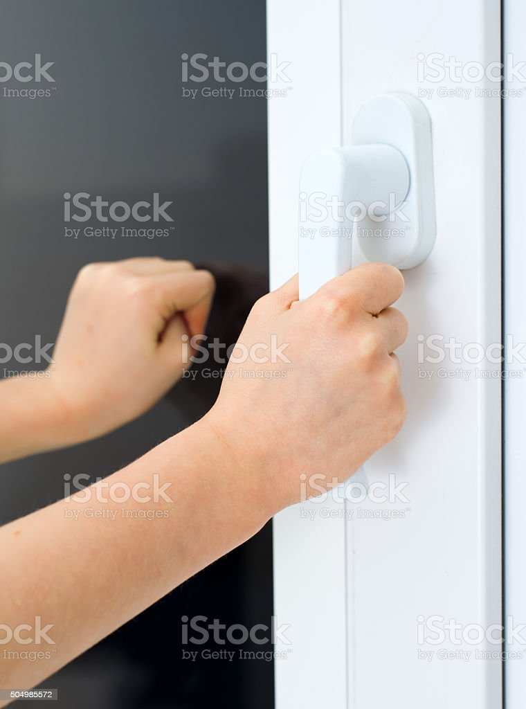 Child tries to open window. Dangerous situation at home. stock photo