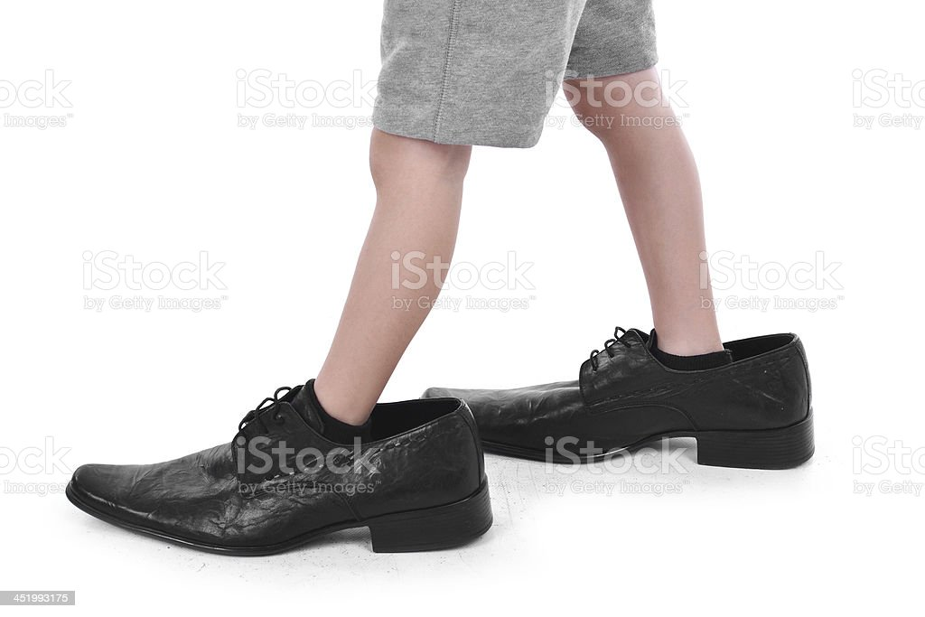 A child trying on big adult leather shoes stock photo