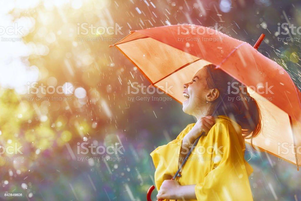 niño bajo la lluvia de otoño - foto de stock