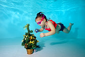 Child underwater in the pool decorates the Christmas tree with Christmas toys. Portrait. Shooting under water. Horizontal orientation.