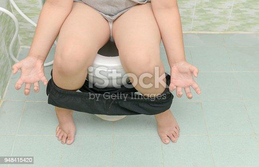 1045838148 istock photo Child unhappy sitting in toilet, diarrhea 948415420
