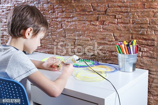 istock Child uses 3D printing pen. Boy making new item. Creative, technology, leisure, education concept 670137302