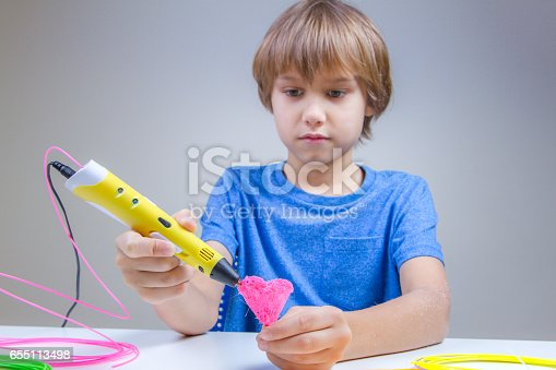 899701486 istock photo Child using 3D printing pen. Boy making heart. Creative, technology, leisure, education concept 655113498