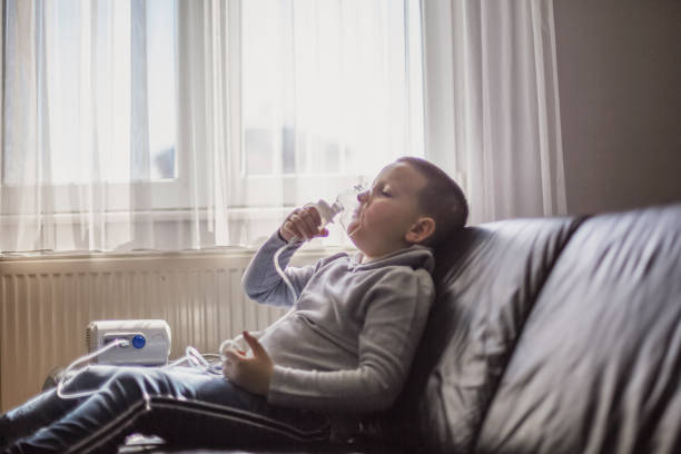 Child using inhaler at home Young boy using inhaler at home respiratory disease stock pictures, royalty-free photos & images