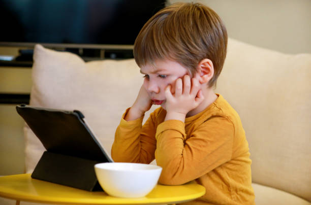 Child using tablet pc on bed at home. Cute boy on sofa is watching cartoon, playing games and learning from laptop. Education, fun, leisure, happiness, modern computer technology and communication. stock photo