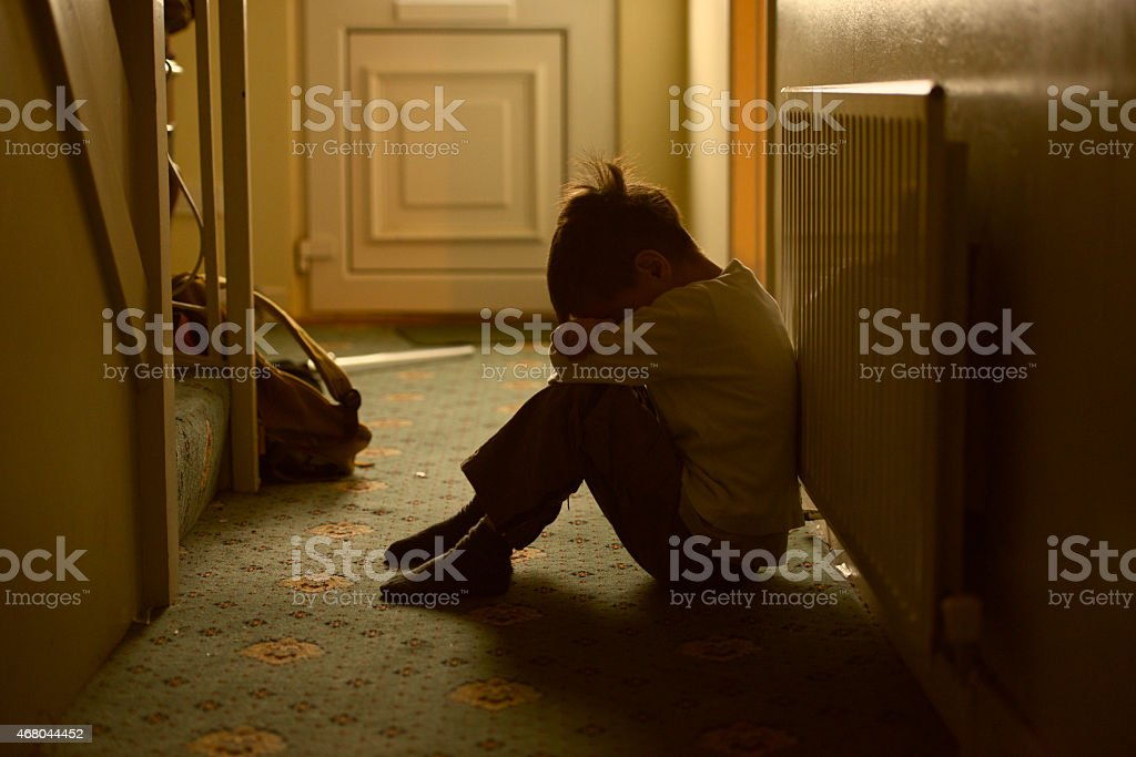 child victim of maltreatment family sad child with his head between his legs left alone at home 2015 Stock Photo