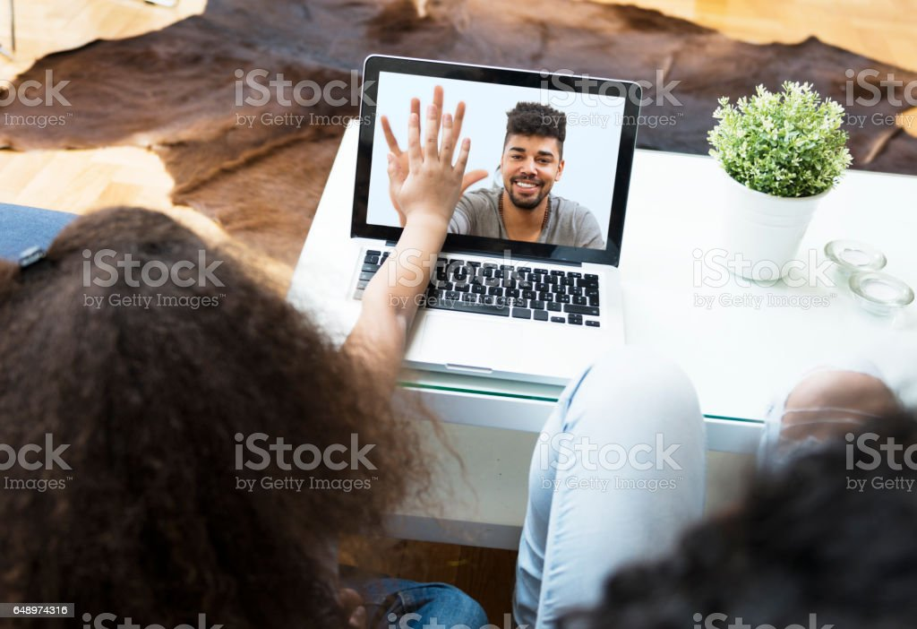 Child video chatting over a laptop with her father stock photo