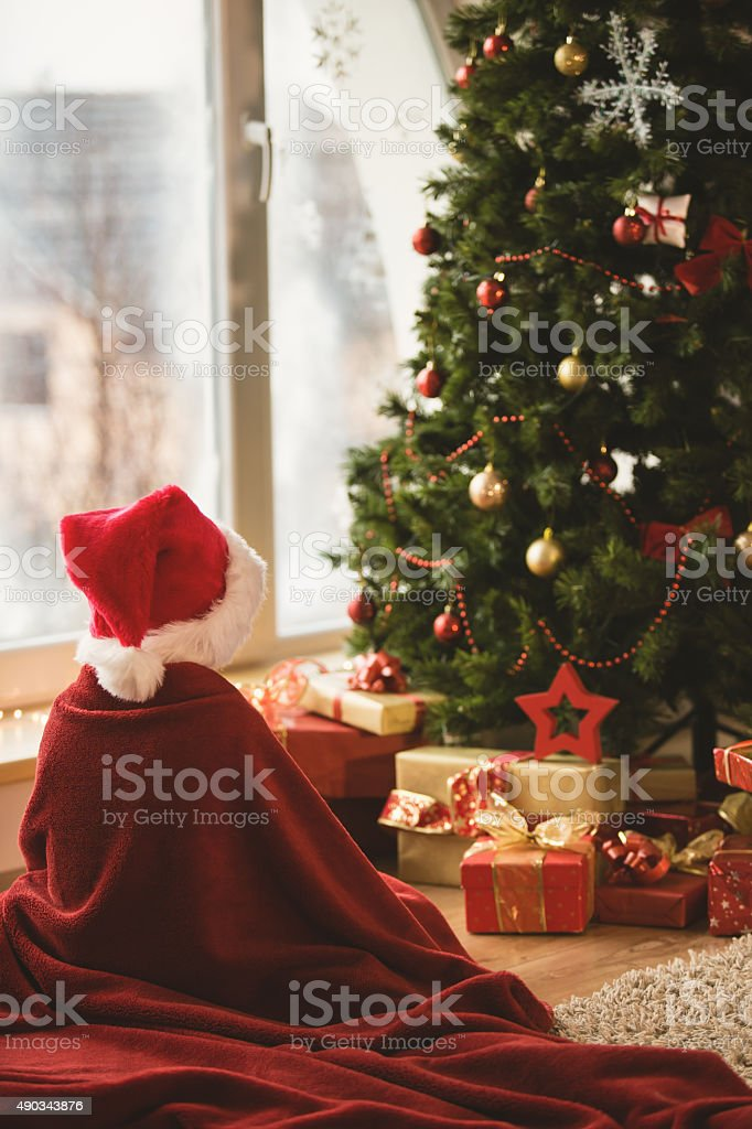 Child waiting Santa by the Christmas tree stock photo