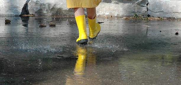 child walking in the rain stock photo
