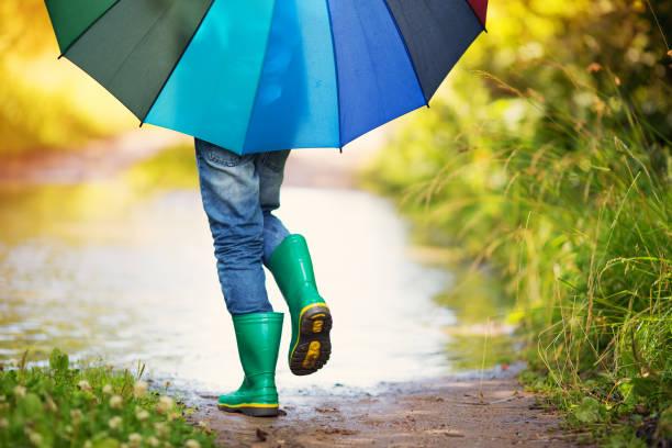 kind zu fuß in gummistiefel in pfütze auf regenwetter - sonnendusche stock-fotos und bilder