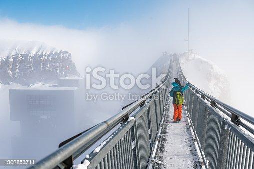 istock Child walking on the bridge. Winter landscape. Glacier 3000, les Diablerets, Switzerland. 1302853711