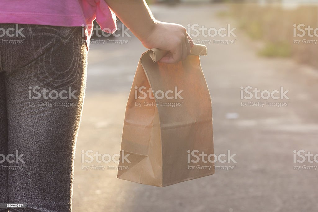 Child walking to school, with lunch bag stock photo