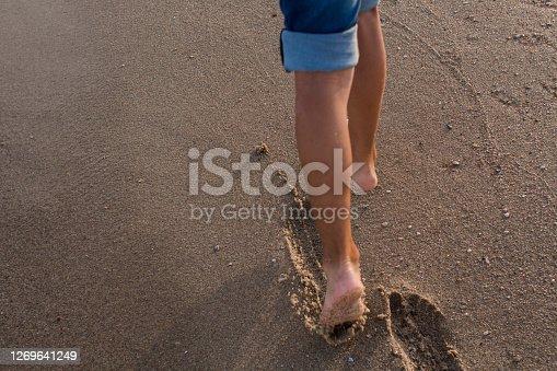 child walks along sandy sea beach