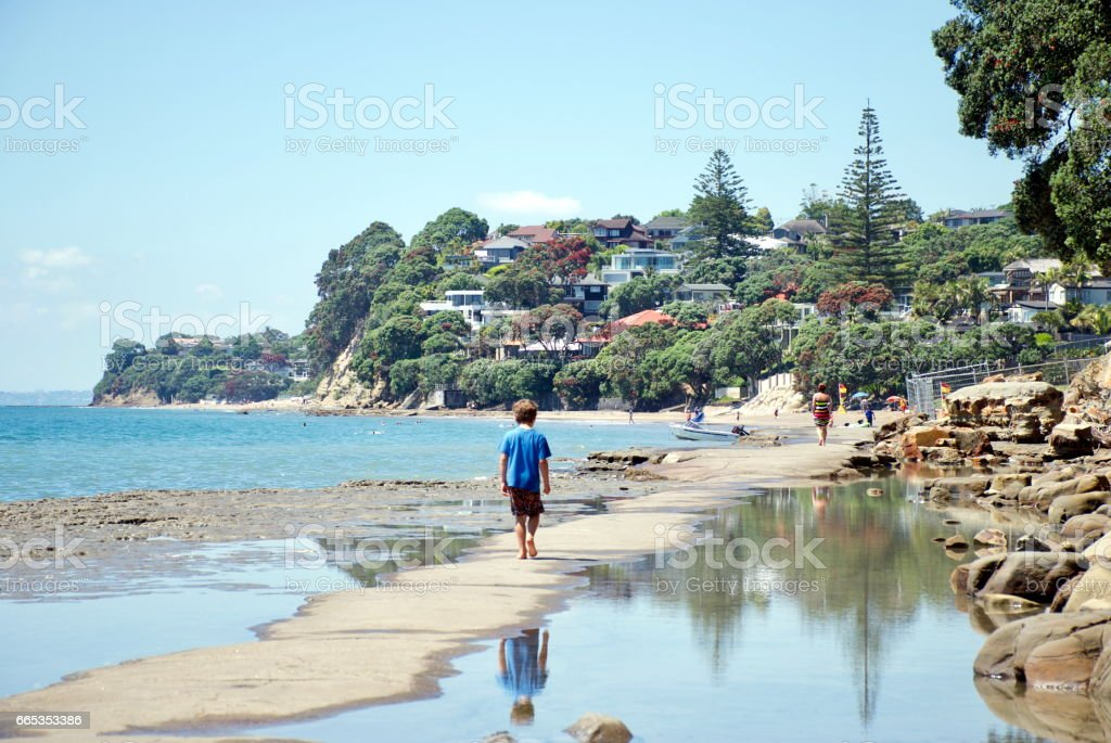 A Child Walks on a Concrete Walkway in the Sea stock photo