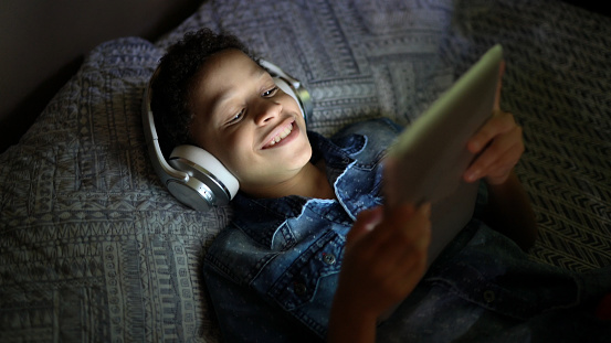 Child watching a movie using digital tablet at bed