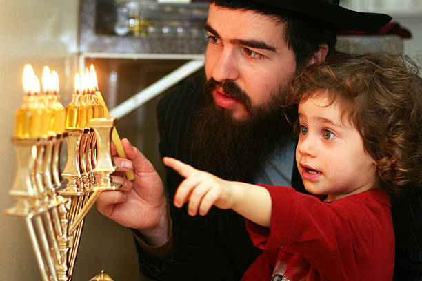 child watching father lighting the menorah - hanukkah stock pictures, royalty-free photos & images