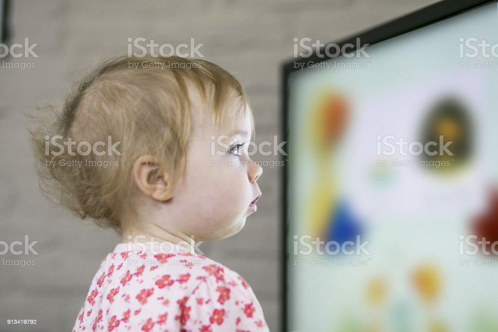 Kind vor dem Fernseher auf großen Plasmabildschirm – Foto