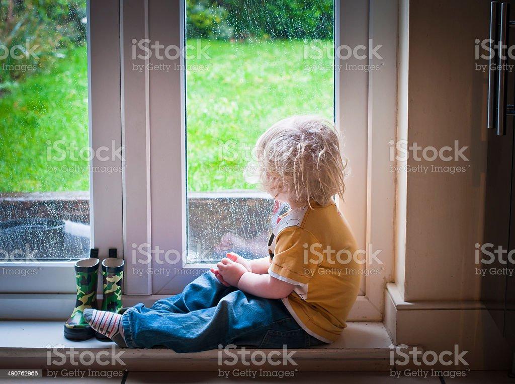 Criança observando a chuva - foto de acervo