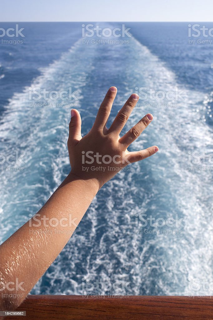 Child waving from the deck of a cruise ship. stock photo