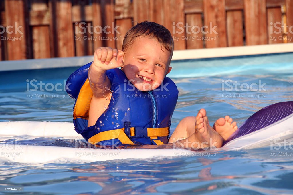Child Wearing a Blue Life Jacket in Swimming Pool royalty-free stock photo