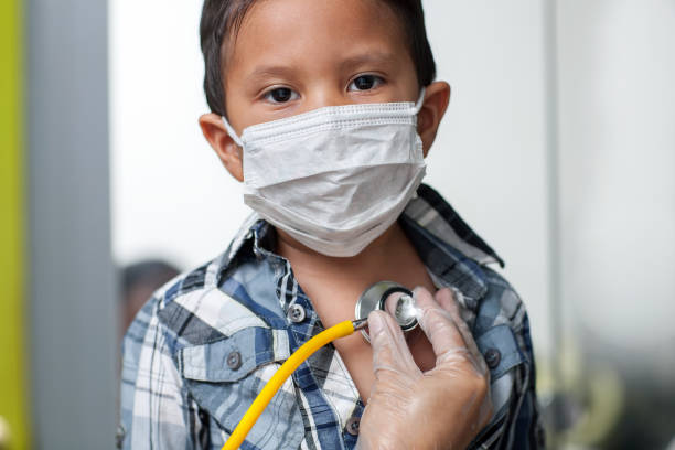 Child wearing a medical mask to prevent spread of virus is getting a heart screening with stethoscope placed on chest. stock photo