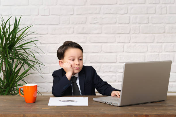 Child wearing a suit like a businessman and he work in his office. stock photo