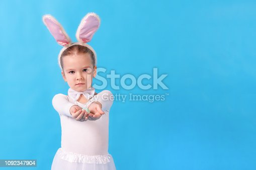 155096501 istock photo A child wearing a white rabbit. A little girl stretches an Easter egg in her hands. Cute bunny, holiday symbol. Bright photo on a blue background, with copy space. 1092347904