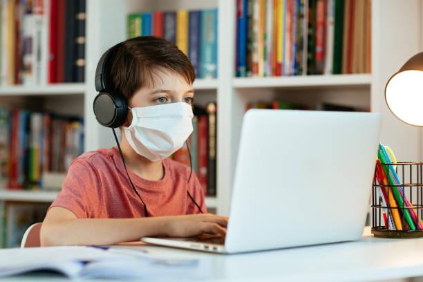 kind trägt gesichtsmaske lernen zu hause. - homeschooling stock-fotos und bilder