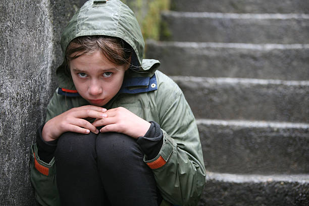 child wearing green coat sitting on stairs - disinherit stock pictures, royalty-free photos & images
