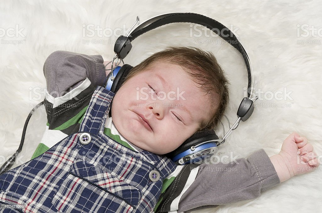 Child wearing headphones and listening to music stock photo