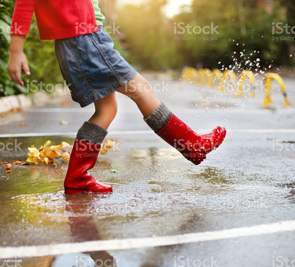 Child wearing red rain boots jumping into a puddle stock photo