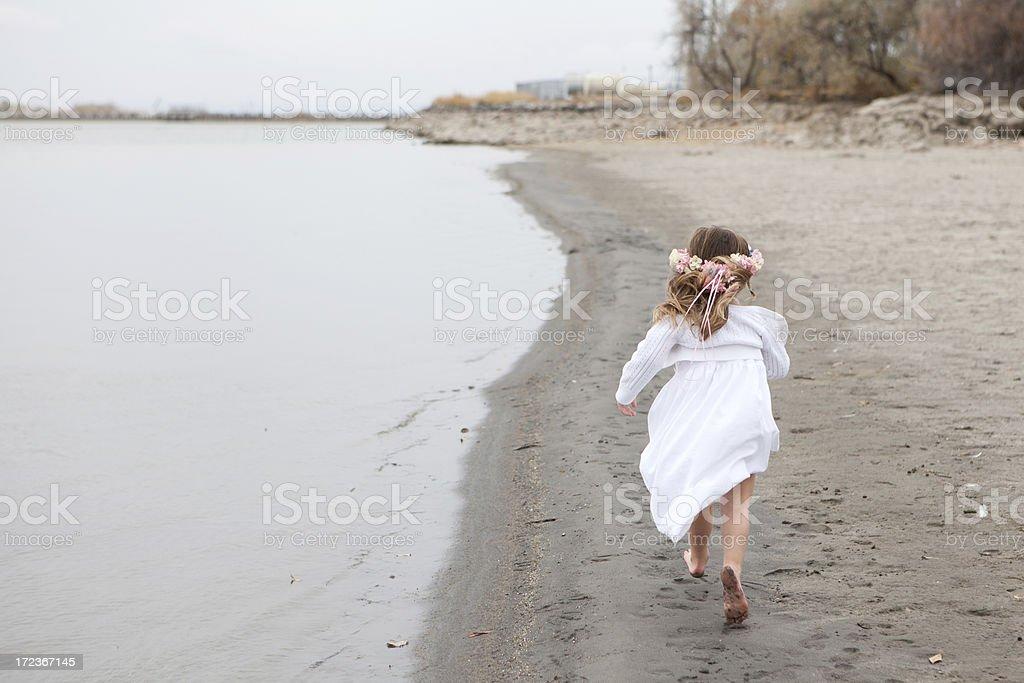 Ребенка носить белое платье и цветы, работающие на пляж стоковое фото