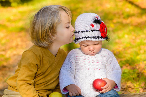 bambino whisper - kids kiss embarrassed foto e immagini stock