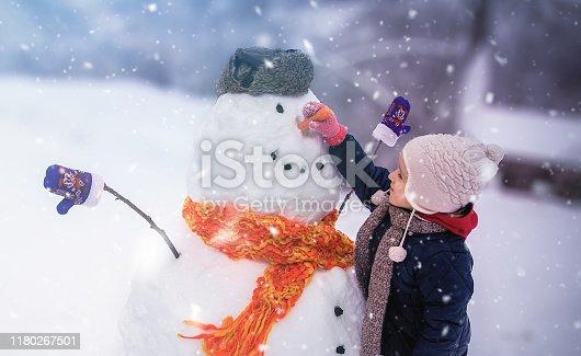 Child sculpts a snowman in a park