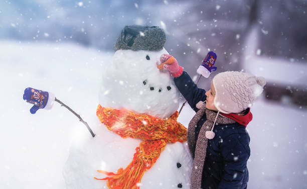 Child Winter Outdoor Fun Child sculpts a snowman in a park snowman stock pictures, royalty-free photos & images