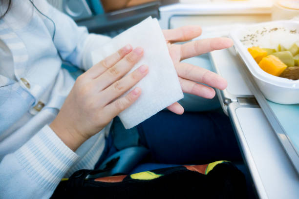 Child Wiping Hands on Passenger Airplane Before Eating Airline Food stock photo