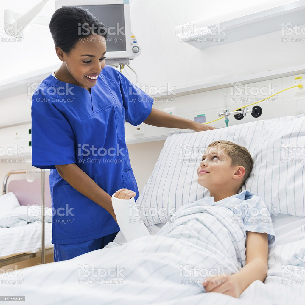 Child with a cast in a hospital bed with a blue clad nurse stock photo
