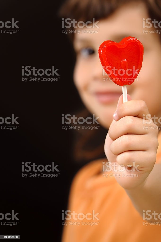Child with a red heart lollipop royalty-free stock photo