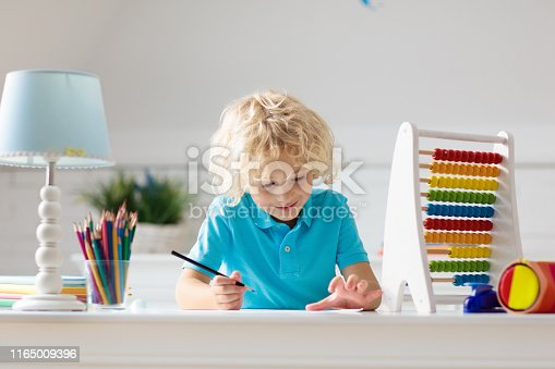 istock Child with abacus doing homework after school. 1165009396