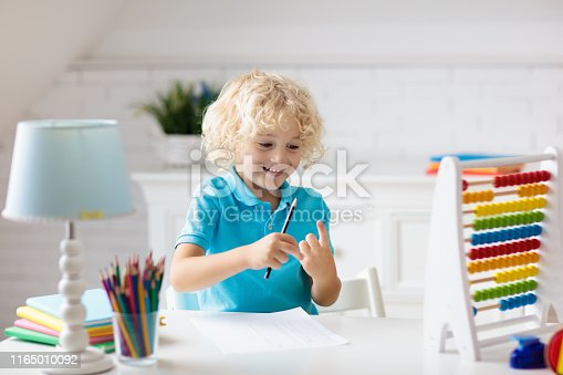 istock Child with abacus doing homework after school. 1165010092