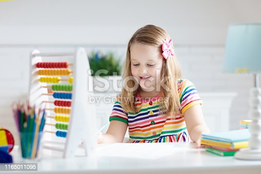 istock Child with abacus doing homework after school. 1165011095