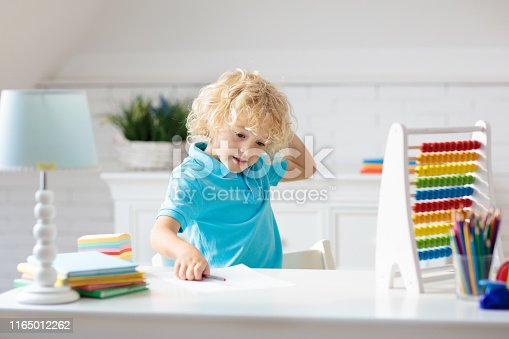 istock Child with abacus doing homework after school. 1165012262