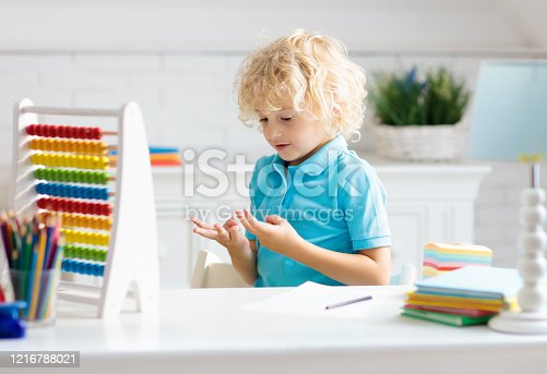 Child doing homework at home. Little boy with wooden colorful abacus doing math exercise learning addition and counting. Kids study and learn. Preschooler kid writing and reading. Back to school.