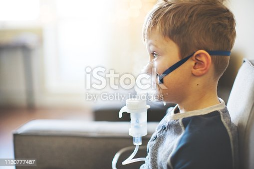 Child with asthma inhaler at home