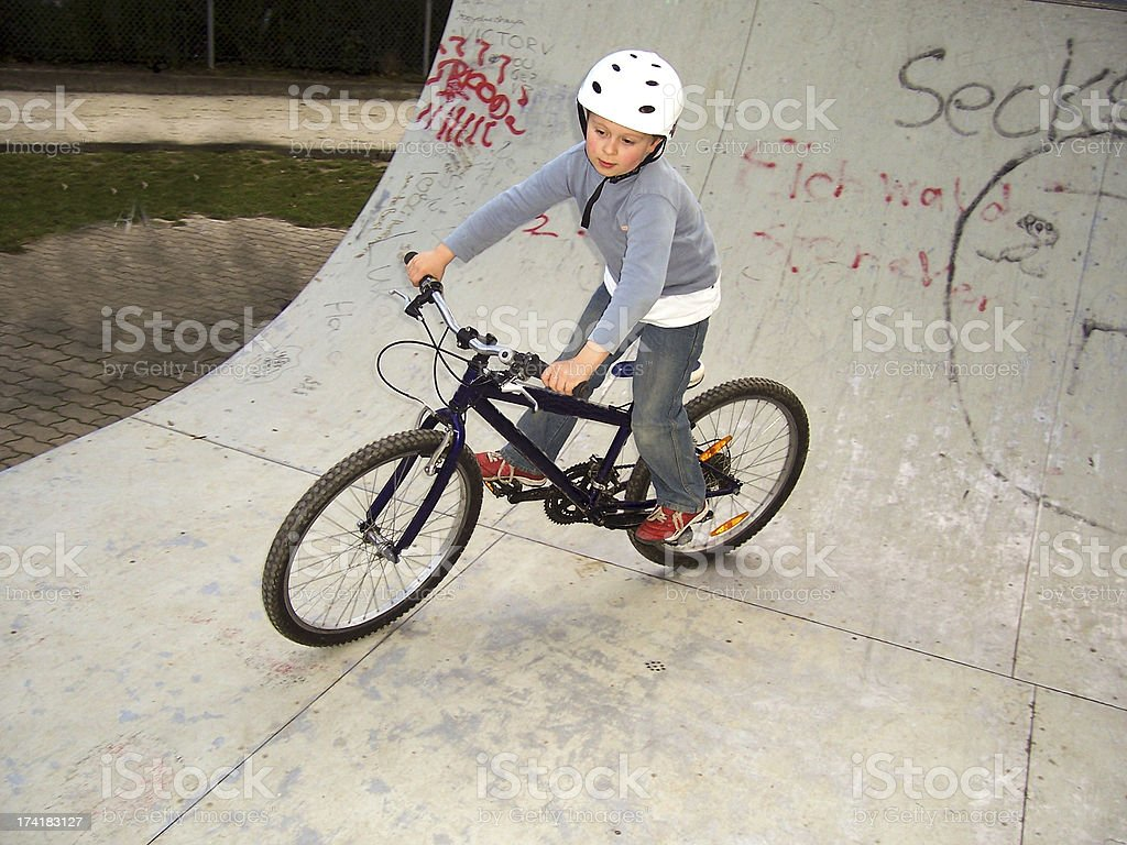 child with bike in the half pipe royalty-free stock photo