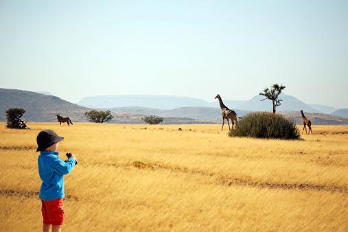 Child with binoculars watching animals on safari in Africa